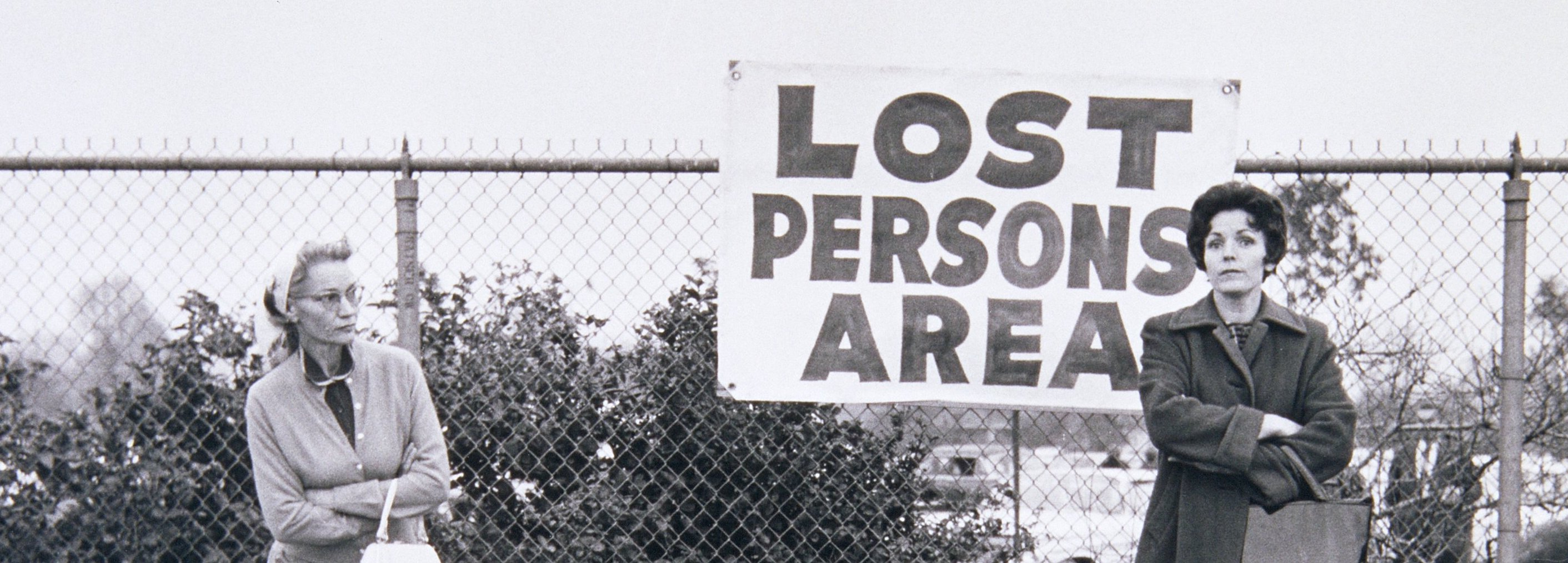 "a black and white photo of several women standing beside a chainlink fence and a handmade sign which reads ""Lost Persons Area"""